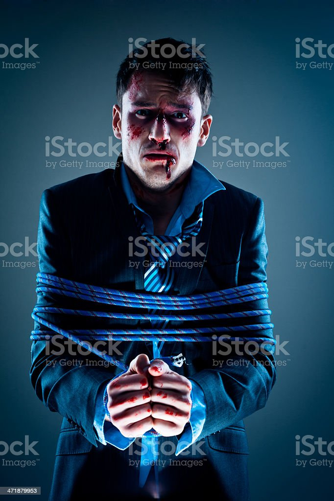 Portrait of depressed businessman tied up with rope. Studio shot,...