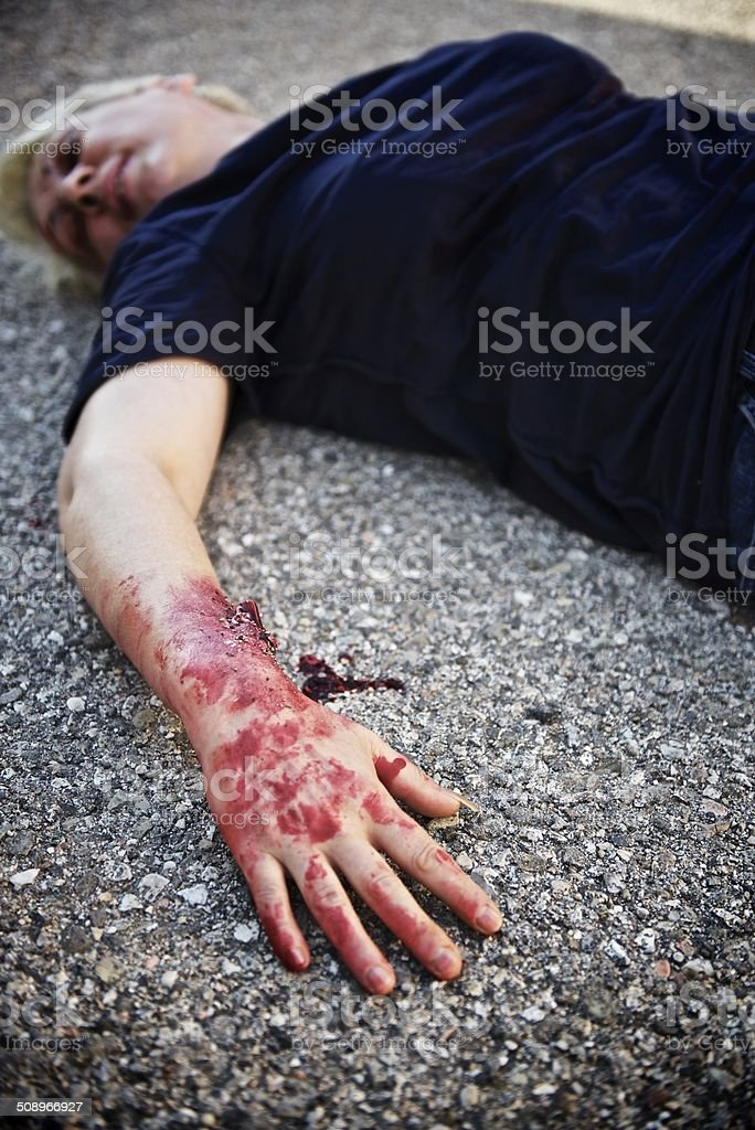 Wounded woman lying on the ground after a car accident