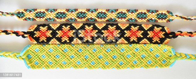 Woven friendship bracelet with bright colorful pattern in boho or bohemian style, handmade of thread isolated on white background