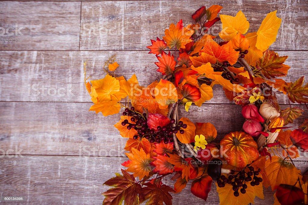 Woven wreath decorated orange leaves, autumn vegetables stock photo