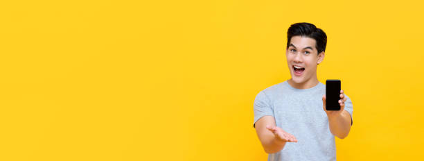 Wow excited young Asian man showing mobile phone with open hand stock photo