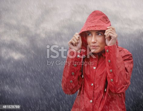 Cropped shot of an attractive young woman standing out in the elements while wearing a red raincoat