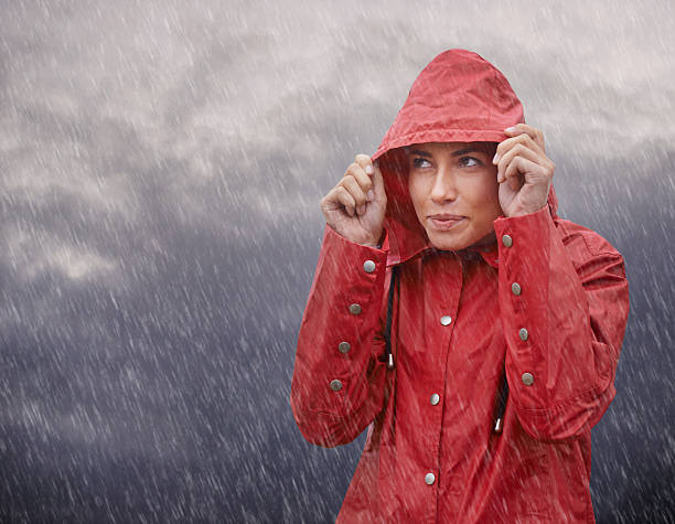 Wow, I'm glad I wore my raincoat! Cropped shot of an attractive young woman standing out in the elements while wearing a red raincoat waterproof clothing stock pictures, royalty-free photos & images