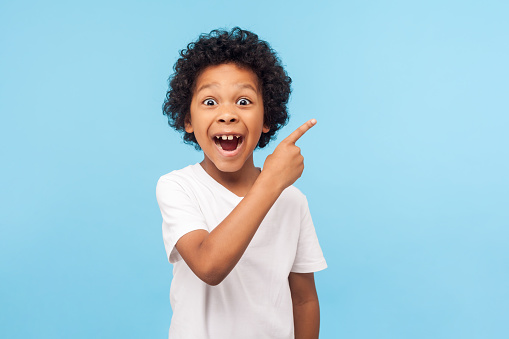 Wow look, advertise here! Portrait of amazed cute little boy with curly hair pointing to empty place