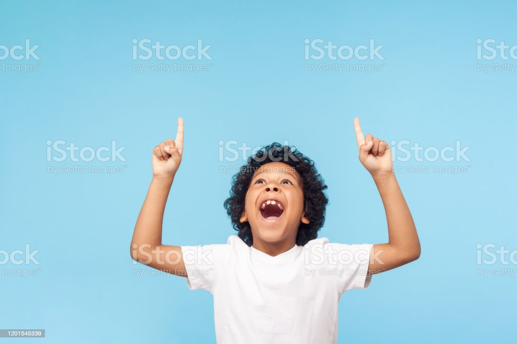 Wow, look up! Portrait of amazed little boy pointing up to empty place on blue background, expressing shock Wow, look up! Portrait of amazed little boy pointing up to empty place on blue background, expressing shock surprise with wide open mouth and showing copy space for advertisement. indoor studio shot Above Stock Photo