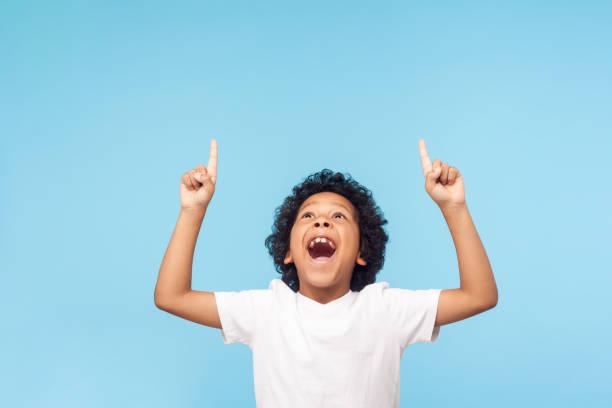 uau, olhe para cima! retrato de menino espantado apontando para lugar vazio em fundo azul, expressando choque - excitação - fotografias e filmes do acervo
