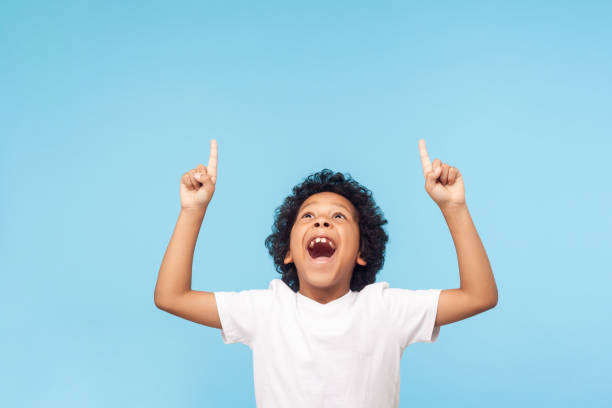 Wow, look up! Portrait of amazed little boy pointing up to empty place on blue background, expressing shock Wow, look up! Portrait of amazed little boy pointing up to empty place on blue background, expressing shock surprise with wide open mouth and showing copy space for advertisement. indoor studio shot excited stock pictures, royalty-free photos & images