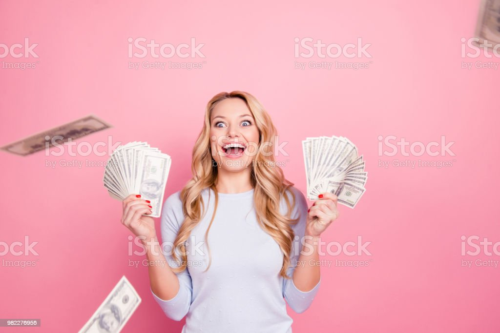 Wow, omg! Portrait of impressed glad  girl having a lot of flying money around her, having unbelievable unexpected reaction, isolated on pink background foto stock royalty-free