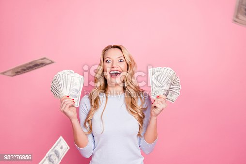 istock Wow, omg! Portrait of impressed glad  girl having a lot of flying money around her, having unbelievable unexpected reaction, isolated on pink background 982276956