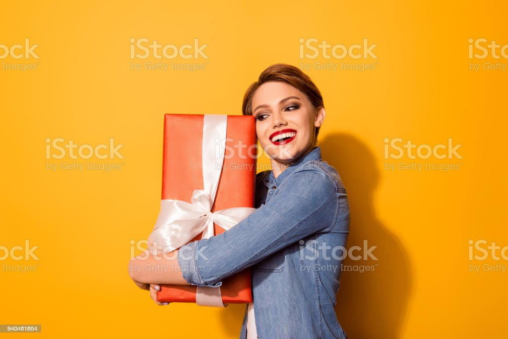 Wow! That`s for me! Happy pretty young woman is holding red box with...