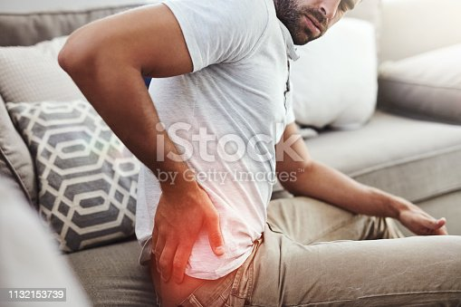 Cropped shot of an unrecognizable young man holding his lower back in discomfort due to pain