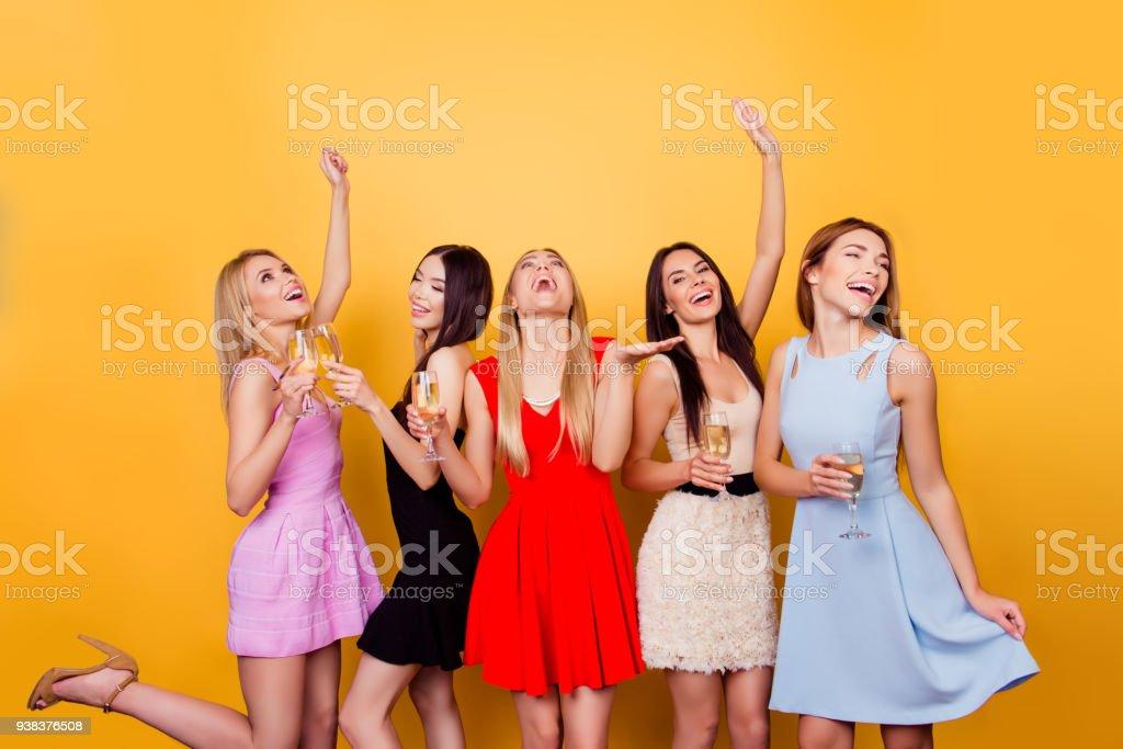 Wow! Ja! Prost auf die Öffnung der Traumort! Fünf Freundinnen begeisterte sind alle in bunten Kleidern, so erstaunt, festlich, tanzen und Spaß, Leerzeichen kopieren Toasten, – Foto