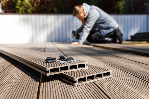 wpc terrace construction - worker installing wood plastic composite decking boards stock photo