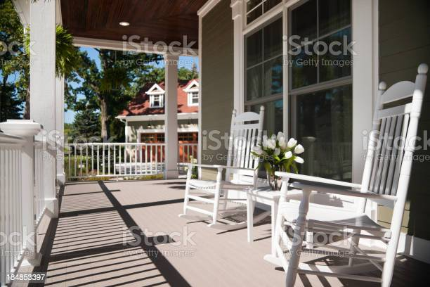 Summers day on the front wrap-around porch with two beautiful white enamel chairs and a vase of tulips. Focus on the foreground.