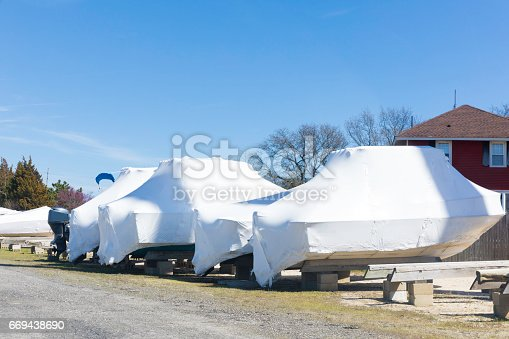 A group of boats are outdoors wrapped in plastic shrink wrap for dry dock winter storage. shot taken with Canon 5D Mark lV.
