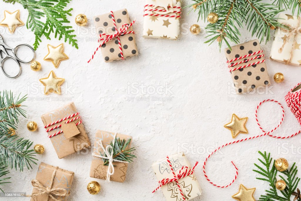 Wrapped Christmas gift boxes, decorations, twine & spruce on white background. stock photo