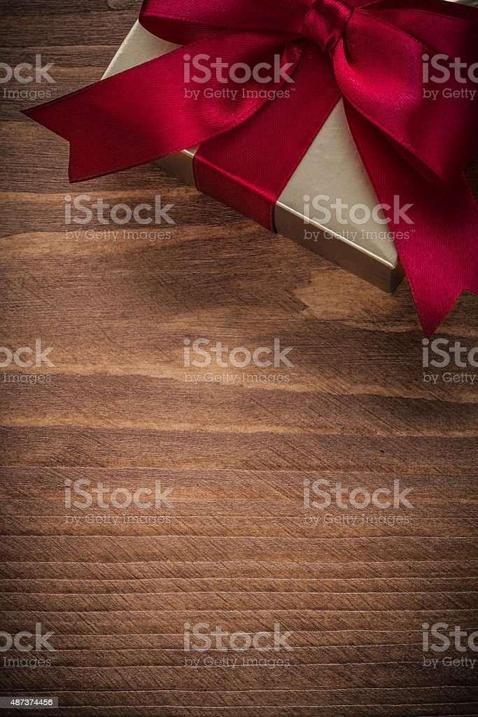 Wrapped glittery gold gift container on vintage wooden board stock photo