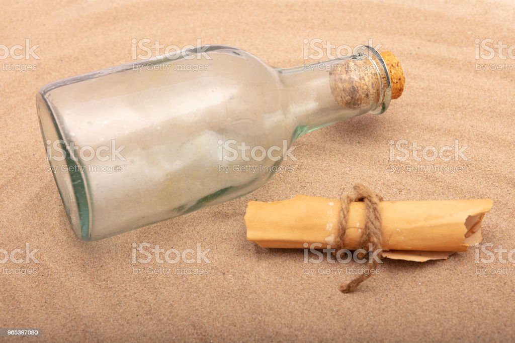 Wrapped message beside an old bottle on the sand of a beach zbiór zdjęć royalty-free