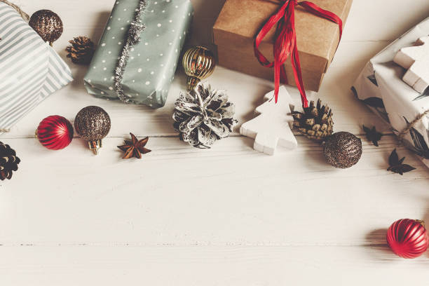 wrapped present boxes with ornaments pine cones anise on white wooden background top view, space for text. christmas flat lay. seasonal greetings card. happy holidays. stock photo