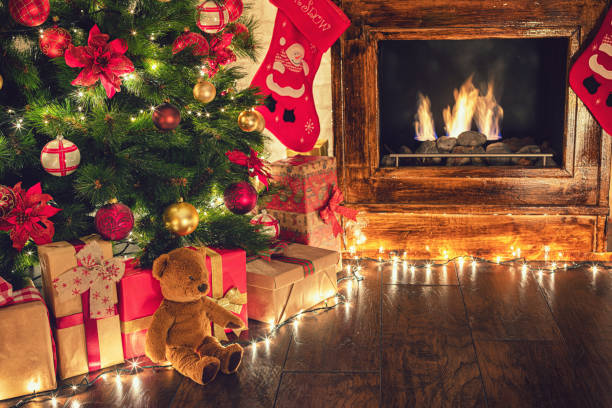 Wrapped presents under the Christmas tree in a cozy festive atmosphere Wrapped presents under the Christmas tree in a cozy festive atmosphere christmas teddy bear stock pictures, royalty-free photos & images