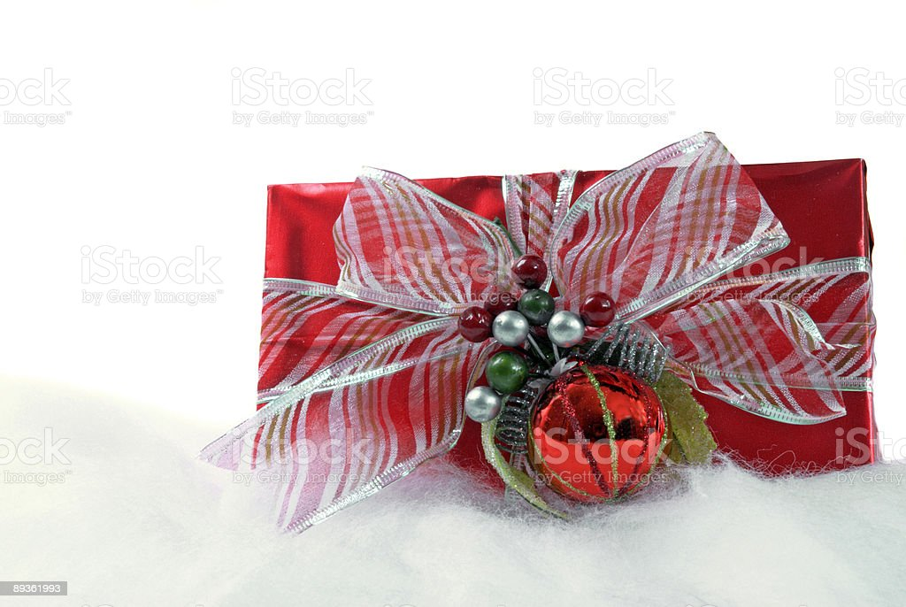 Wrapped red Christmas present on a bed of artificial snow royalty free stockfoto