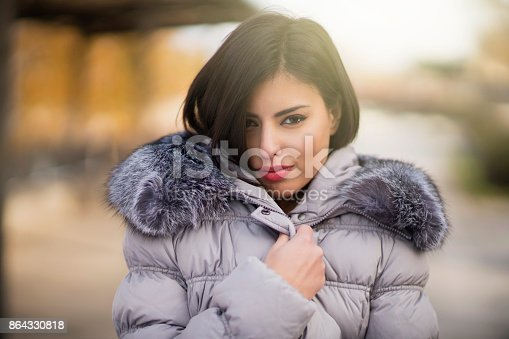 Portrait of a beautiful young woman wrapped up warm in furry winter jacket.