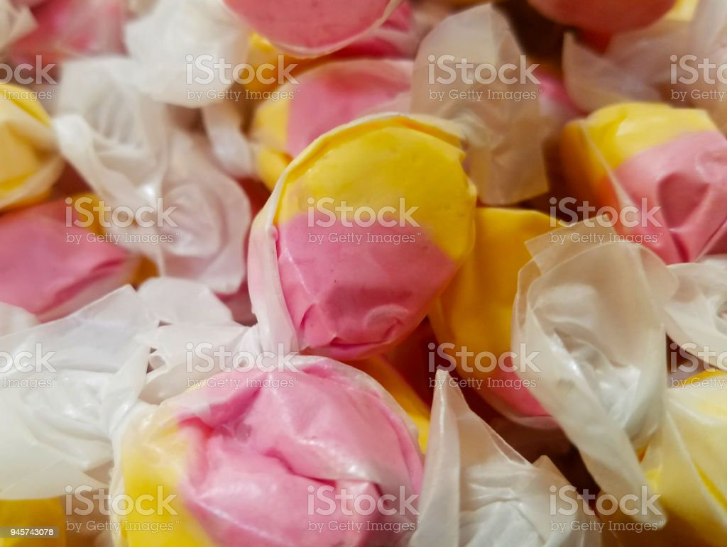 Wrapped yellow and pink taffy candies in bulk stock photo