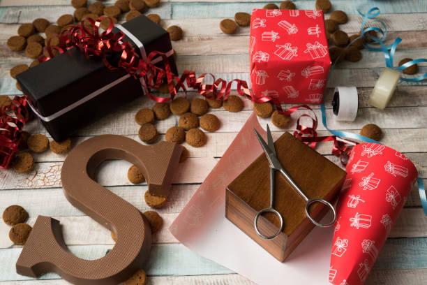 verpakken van een gift voor nederlandse evenement sinterklaas, met kruidnoten, cookies - cadeau sinterklaas stockfoto's en -beelden