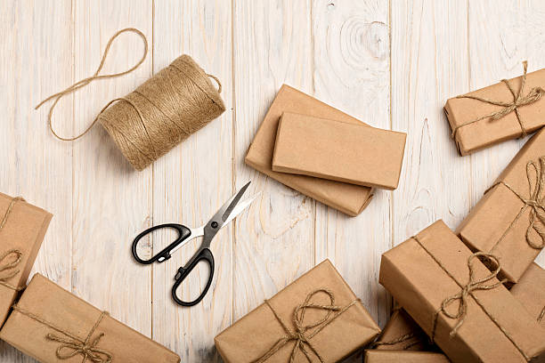 wrapping christmas gifts in kraft paper and rope. - bastelkarton stock-fotos und bilder