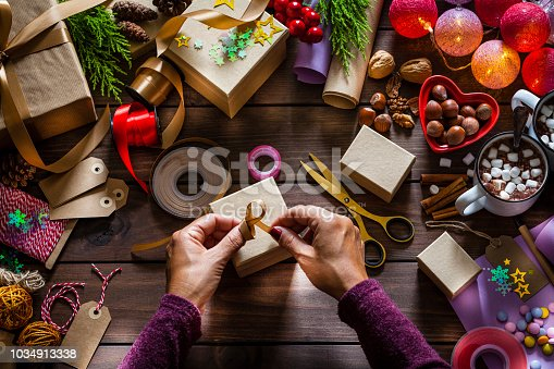 Top view of a wooden table filled with gift boxes, ribbons, Christmas lights, strings, scissors and other items for wrapping Christmas presents. At the center of the frame is a gift box ready for been wrapped and two female hands are making a ribbon on the box. Low key DSRL studio photo taken with Canon EOS 5D Mk II and Canon EF 100mm f/2.8L Macro IS USM.