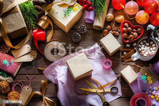 Top view of a wooden table filled with gift boxes, ribbons, Christmas lights, strings, scissors and other items for wrapping Christmas presents. At the center of the frame is a gift box ready to be wrapped. DSRL photo taken with Canon 5D Mk II and Canon 100mm Macro lens.