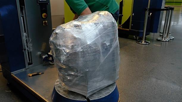 einwickeln gepäck gepäck tasche am flughafen-terminal - gepäck verpackung stock-fotos und bilder