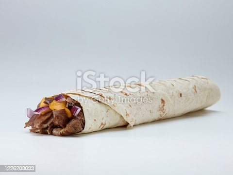 Burrito and shawarma wraps with beef and pork vegetables on wooden table.