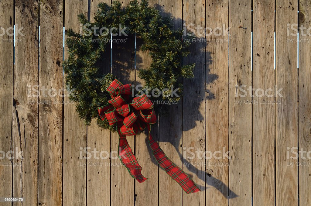 wreath hanging on wood fence outdoors stock photo