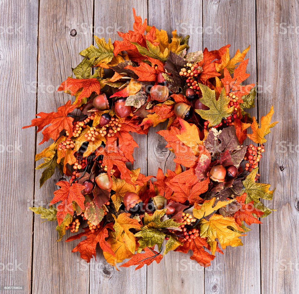Wreath made of autumn leaves and acorns on wood stock photo