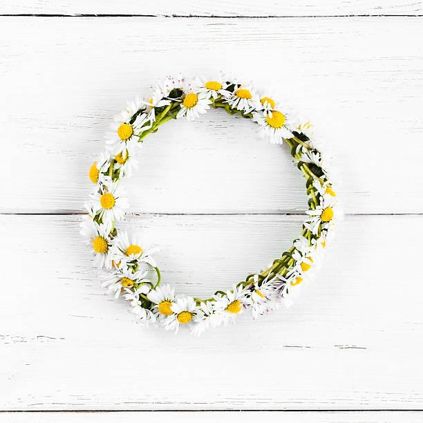 Kranz gemacht aus Gänseblümchen Blumen auf weißer hölzerner Hintergrund – Foto