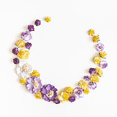 istock Wreath made of purple and yellow flowers on white background. Flat lay, top view, copy space, square 1133779652