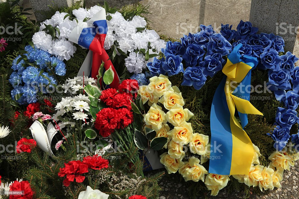 Wreathes with Russian and Ukrainian national flags. stock photo