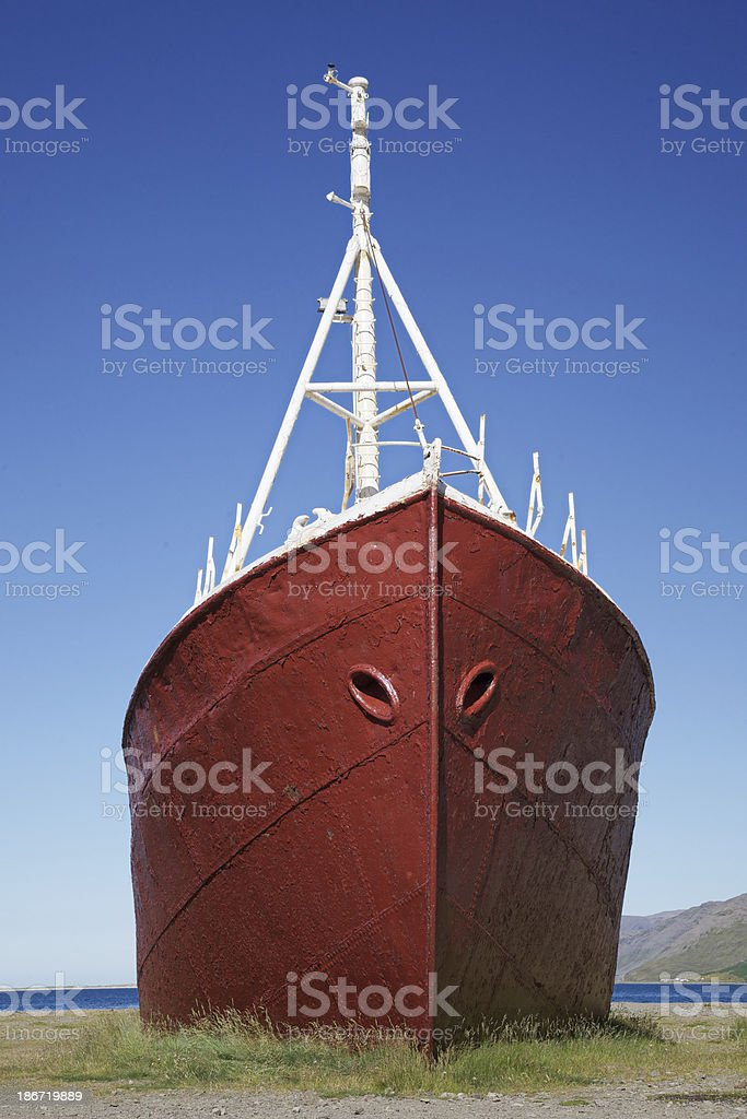 Wreck of a red vessel lying the Westfjords. Iceland. royalty-free stock photo