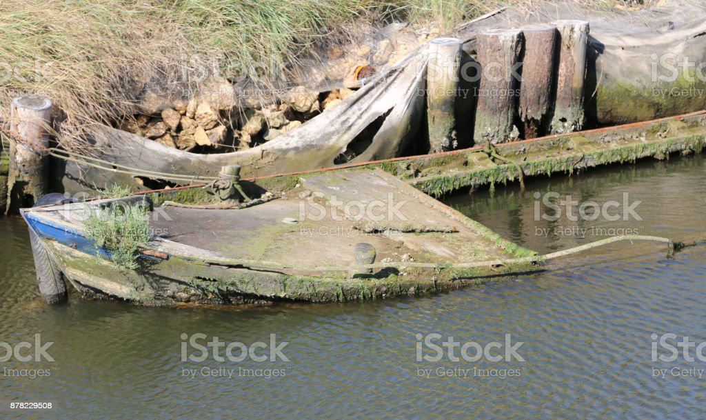 wreck of a sunken fishing boat in the lagoon stock photo