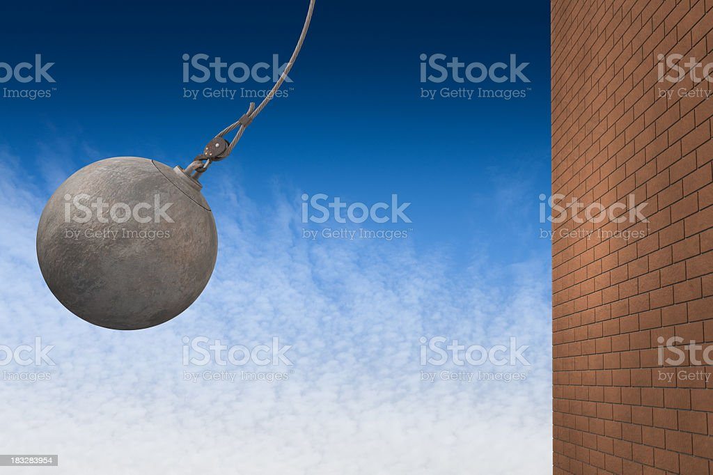 A wrecking ball about to hit a brick wall stock photo