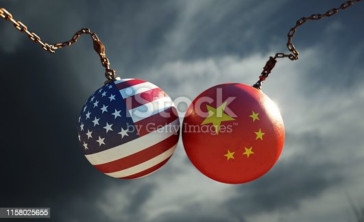 Wrecking balls textured with American and Chinese flags over dark stormy sky. Horizontal composition with copy space and selective focus. Dispute concept.