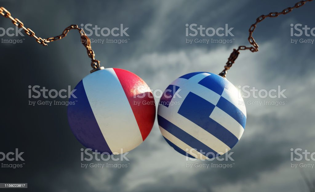 Wrecking balls textured with French and Greek flags over dark stormy...