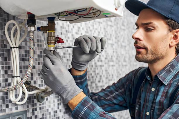 klucz zawsze z tobą. pracownik skonfigurować elektryczny kocioł grzewczy w łazience domu - naprawiać zdjęcia i obrazy z banku zdjęć