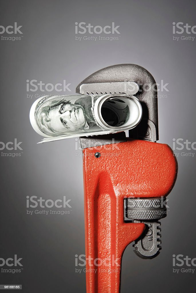 Wrench Holding Dollar Roll royalty-free stock photo