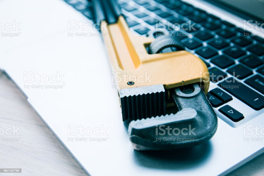 Wrench on computer keyboard stock photo