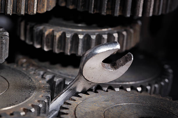 A wrench stuck in the middle of some gears stok fotoğrafı