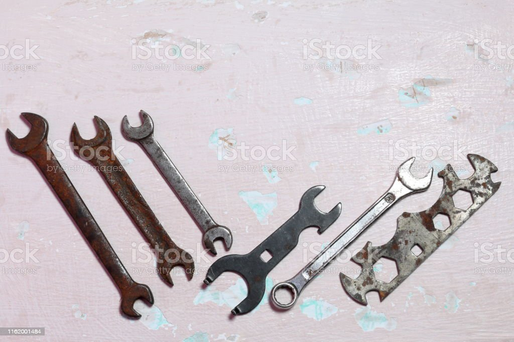 Wrenches for different sizes. Worn and covered with corrosion. Lie on...