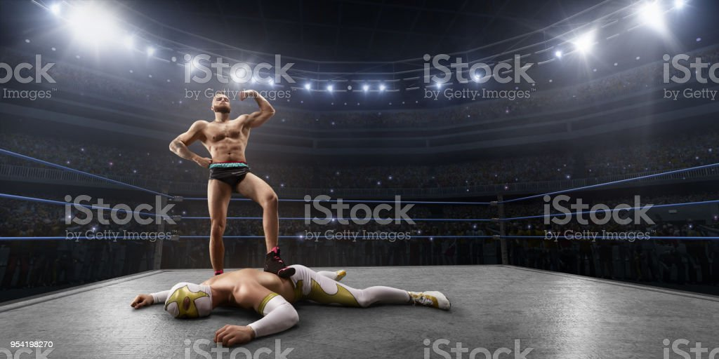 Wrestling show. Two wrestlers in a bright sport clothes and face mask fight in the ring stock photo