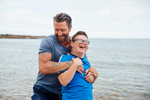 A shot of a caucasian father and son with down syndrome having a fun fight on the beach.